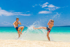Garçons de l'adolescence heureux ayant l'amusement sur la plage tropicale Vacatio d'été Photographie stock libre de droits