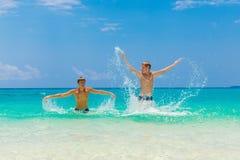Garçons de l'adolescence heureux ayant l'amusement sur la plage tropicale Vacatio d'été Images stock