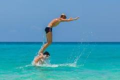 Garçons de l'adolescence heureux ayant l'amusement sur la plage tropicale Vacatio d'été Photo libre de droits