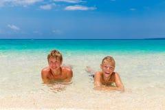 Garçons de l'adolescence heureux détendant sur la plage Mer tropicale dans le backg Photographie stock libre de droits