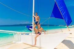 Garçons de l'adolescence heureux sur le voilier sur la plage tropicale Été va Photographie stock libre de droits