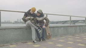 Garçons de l'adolescence vérifiant le support de roue sur le patin extérieur banque de vidéos