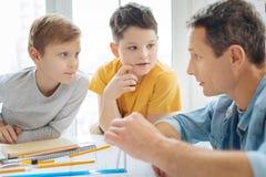 Garçons de la préadolescence causant avec le père tandis qu'il modèle de dessin Images stock