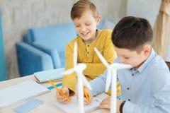 Garçons de la préadolescence joyeux réunissant des croquis des turbines de vent Photo stock