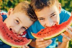 Garçons de sourire mangeant la pastèque Photo libre de droits