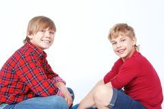 Garçons de sourire s'asseyant sur le plancher Photos libres de droits