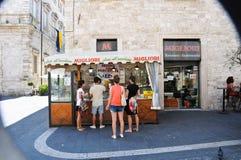 Garçons devant une stalle vendant les olives bourrées Photographie stock libre de droits