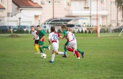 Garçons donnant un coup de pied le football Images libres de droits
