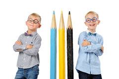 Garçons drôles de portrait jeunes en verres et bowtie posant près des crayons colorés énormes Concept éducatif D'isolement au-des image stock