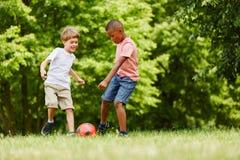 Garçons en voyage de vacances jouant le football Image libre de droits