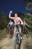 Garçons et bicyclettes d'équitation de fille sur la route de campagne Image libre de droits