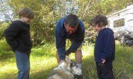 Garçons et chien choyant de papa Image libre de droits