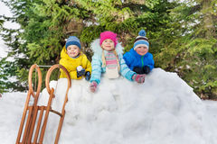 Garçons et fille d'enfants derrière le mur de neige avec des boules de neige Image stock
