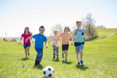 Garçons et filles courant vers le football Images stock