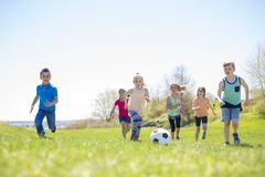 Garçons et filles courant vers le football Photo stock