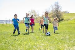 Garçons et filles courant vers le football Photographie stock libre de droits