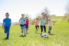 Garçons et filles courant vers le football Images libres de droits