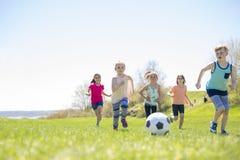 Garçons et filles courant vers le football Image libre de droits