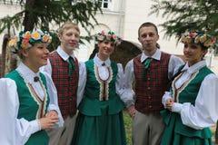 Garçons et filles dans des costumes folkloriques lettons Image stock