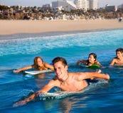 Garçons et filles de surfer d'adolescent nageant la planche de surf d'ove Image libre de droits