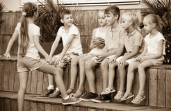 Garçons et filles s'asseyant et jouant avec la boule dehors Images stock