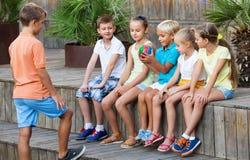 Garçons et filles s'asseyant et jouant avec la boule dehors Image libre de droits