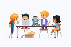 Garçons et filles se tenant et s'asseyant autour du bureau avec les ordinateurs portables et le robot et travaillant sur le proje Photographie stock