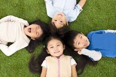 Garçons et filles se trouvant sur l'herbe verte Photos stock