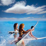 Garçons et surfers de l'adolescence de filles courant sauter sur des planches de surf Photos stock
