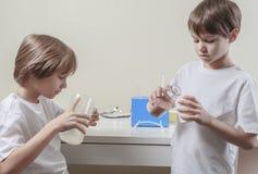 Garçons faisant des expériences de la science réserve vieux d'isolement par éducation de concept images libres de droits