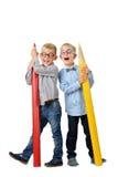 Garçons heureux de portrait intégral jeunes en verres et bowtie posant près des crayons colorés énormes Concept éducatif D'isolem image libre de droits