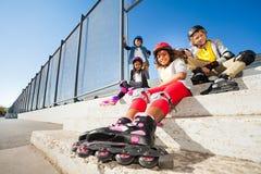 Garçons heureux et filles se reposant après le patinage de rouleau Photos stock