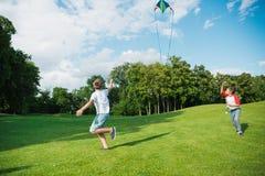 Garçons heureux jouant avec le cerf-volant sur le pré vert en parc Photo libre de droits