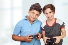 Garçons heureux jouant des jeux vidéo Photographie stock libre de droits