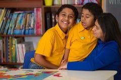 Garçons hispaniques avec la maman dans l'environnement de Maison-école Photographie stock libre de droits