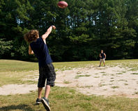 Garçons jetant le football en l'air Photo libre de droits