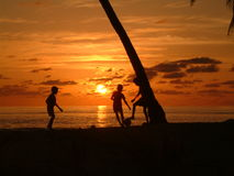 Garçons jouant au coucher du soleil Photographie stock libre de droits