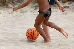 Garçons jouant au football de plage Images stock