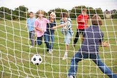 Garçons jouant au football en stationnement Photographie stock libre de droits