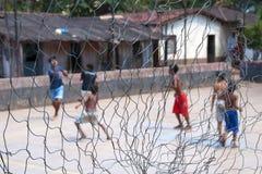 Garçons jouant au football nu-pieds Photographie stock