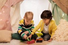 Garçons jouant des blocs de jouet dans la tente d'enfants à la maison Photos stock