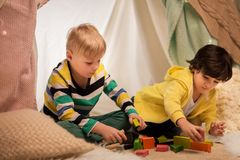 Garçons jouant des blocs de jouet dans la tente d'enfants à la maison Photo stock