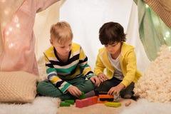 Garçons jouant des blocs de jouet dans la tente d'enfants à la maison Image libre de droits