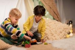 Garçons jouant des blocs de jouet dans la tente d'enfants à la maison Photos libres de droits