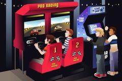 Garçons jouant des courses d'automobiles dans une arcade Photo stock