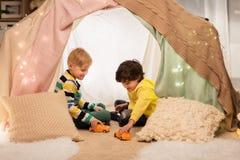 Garçons jouant des voitures de jouet dans la tente d'enfants à la maison Photo stock