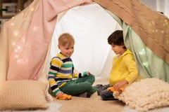 Garçons jouant des voitures de jouet dans la tente d'enfants à la maison Image stock