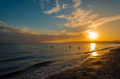 Garçons jouant en mer au coucher du soleil Photos stock