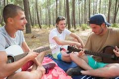 3 garçons jouant la guitare dans la forêt Photo stock