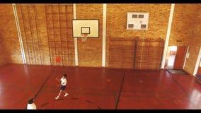 Garçons jouant le basket-ball devant le tribunal banque de vidéos